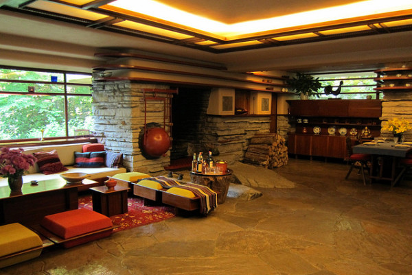 A boulder top, rising unaltered above the level of the first floor, serves as the hearth of the fireplace and the center of Fallingwater. To the left hangs a spherical kettle that can be swung over the fire.